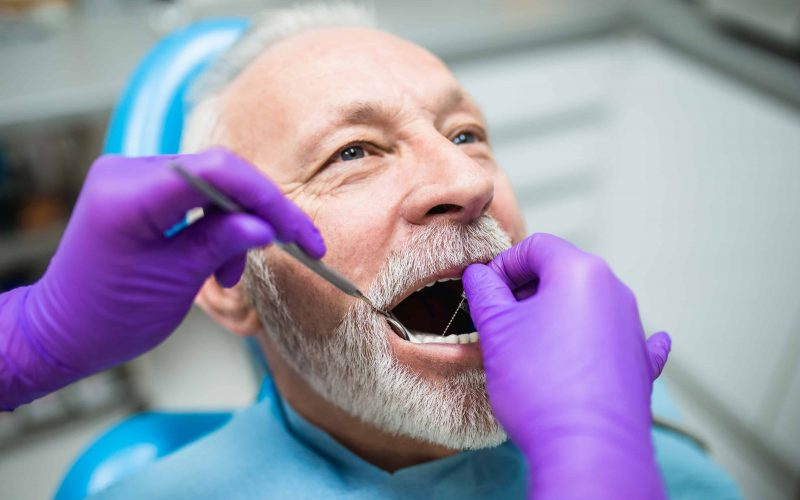 Senior bearded man having dental treatment at dentist's office.